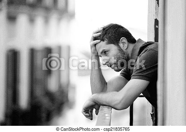 Lonely young man outside at house balcony looking depressed, destroyed, sad and suffering emotional crisis and grief thinking of taking a difficult and important life decision on an urban background in black and white