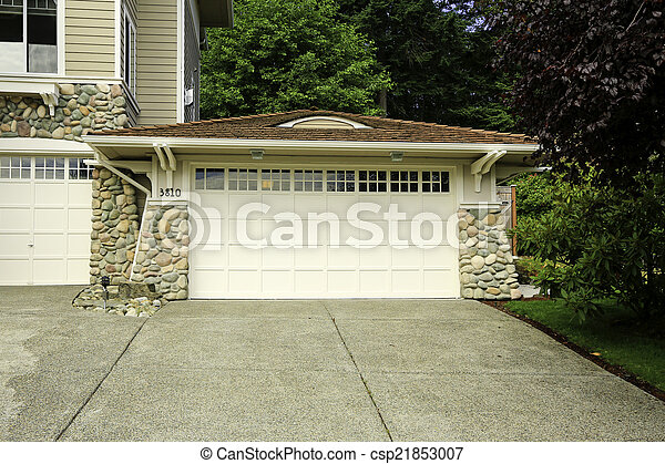 House garage with stone trim and tile roof