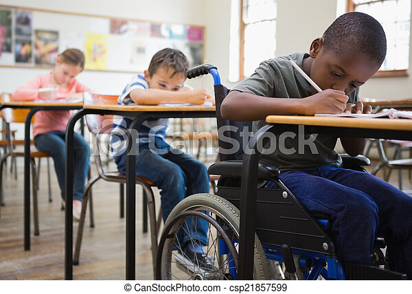 Cute pupils writing at desks in classroom