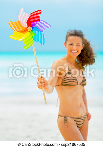 Closeup on happy young woman holding colorful windmill toy