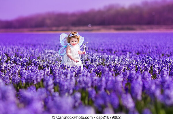 Cute toddlger girl in fairy costume playing with purple flowers - csp21879082