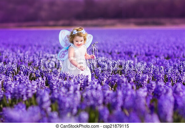 Toddler girl in fairy costume playing in a flower field - csp21879115
