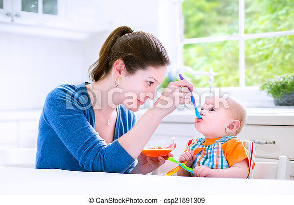 Baby boy eating his first solid food - csp21891309