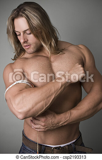 A bodybuilder measuring the increase in his bicep - csp2193313