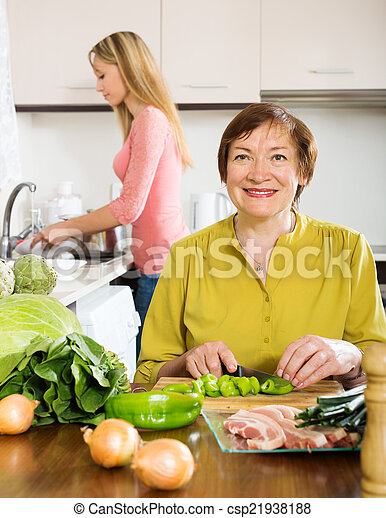 Happy mature woman with adult daughter cooking  together  - csp21938188
