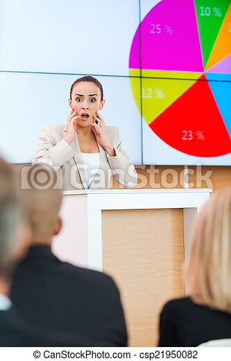 Fear of public speaker. Shocked young woman in formalwear touching her face with hands while standing at the tribune in conference hall with people on foreground