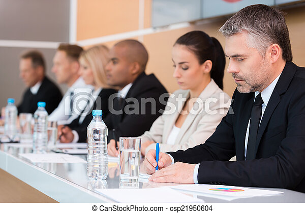 Business conference. Side view of business people writing something in their note pads while sitting in a row
