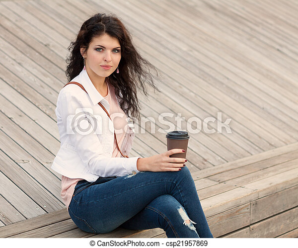 Beautiful tall girl with long hair brunette in jeans standing on old wooden planks with a cup of coffee in hand on a warm summer evening