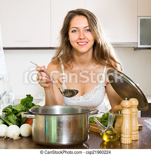 Woman cooking soup in kitchen
