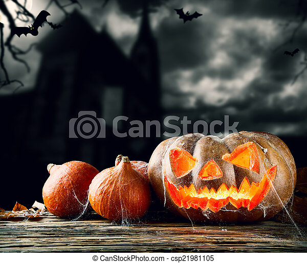 Concept of halloween pumpkins on wooden planks. Blur scary churche on background