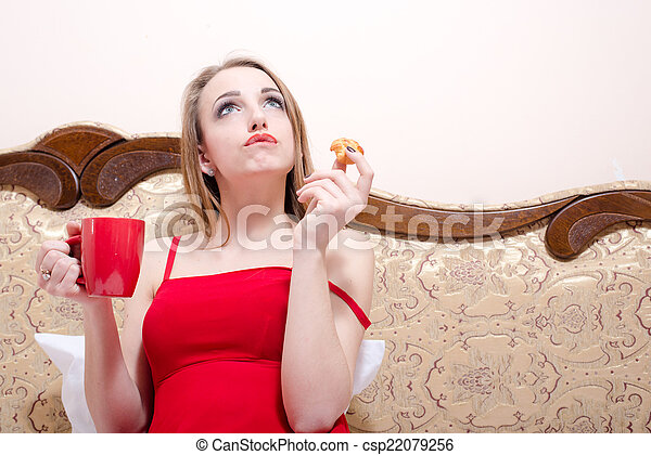 sitting on bed or coach in red dress drinking tea and eating cake beautiful blonde young woman having fun looking up at copy space closeup portrait picture