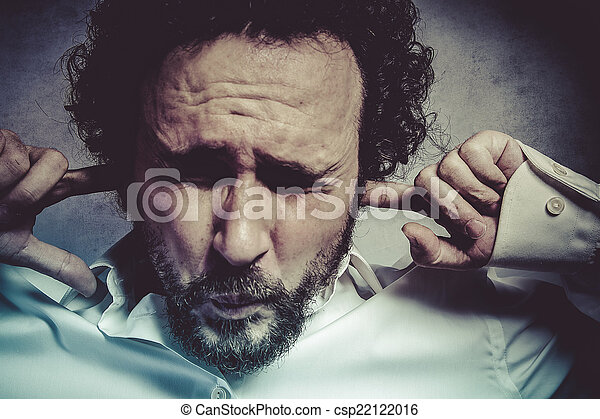 Businessman covering his ears, man in white shirt with funny exp