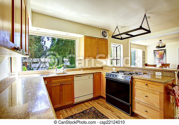 Simple kitchen interior with wooden cabinets and granite tops
