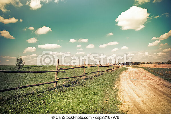 Sunny day in countryside. Empty rural road going through summer landscape under blue cloudy sky. Nature background in vintage style