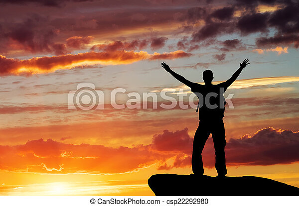 Silhouette of a man on a mountain top on sunset sky background