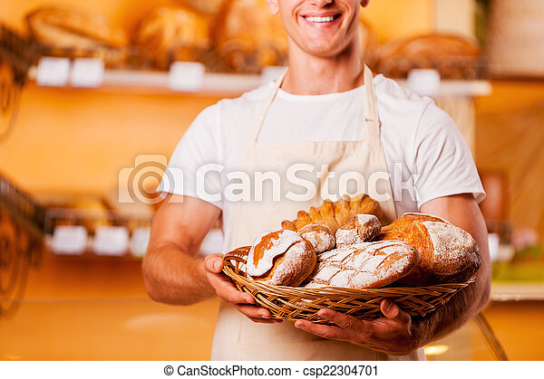 The freshest bread for you. Cropped image of young man in apron holding basket with baked goods and smiling while standing in bakery shop