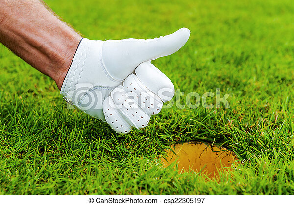 Good job! Close-up of male hand in golf glove gesturing thumb up near the hole in gold course