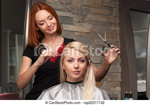 Happy young woman getting new haircut by hairdresser at parlor. redhead hairdresser cutting client\'s hair in beauty salon