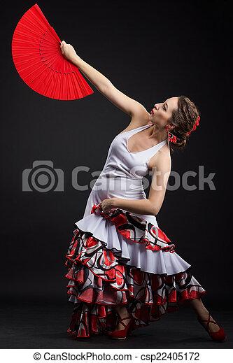 Young spanish woman dancing flamenco on black