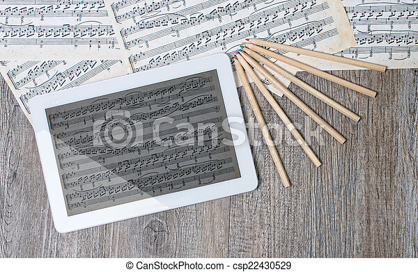 musical scores with a digital tablet placed on an ancient table