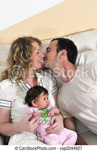 indoor portrait with happy young family and  cute little babby - csp2244927