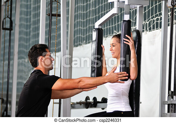 woman in the fitness gim working out with personal trainer - csp2246331