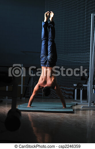 young man performing handstand in fitness studio - csp2246359
