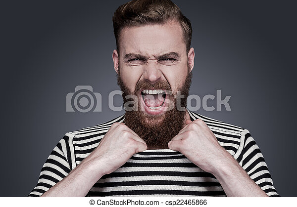 Unleashed emotions. Furious young bearded man in striped clothing stretching his collar and shouting while standing against grey background