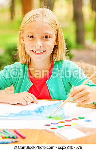I love drawing! Cute little girl drawing something on paper and smiling while sitting at the table and outdoors