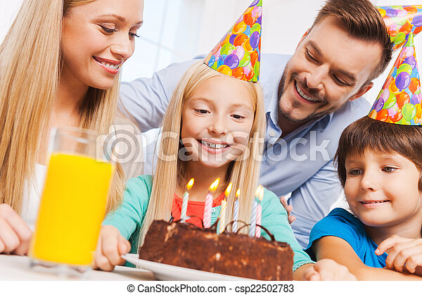 Happy birthday! Happy family of four celebrating birthday of happy little girl sitting at the table with birthday cake on it