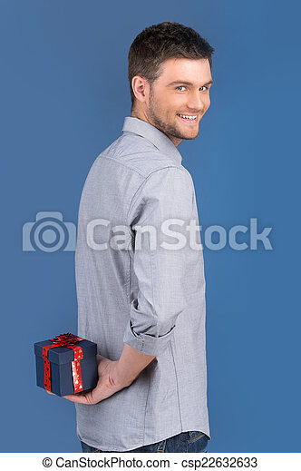 side view of smiling guy holding gift in blue box. waist up of happy male carrying blue box on blue background