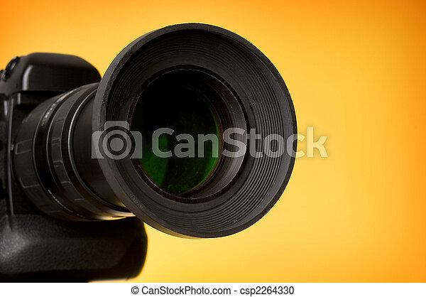 Professional digital camera over orange background. Close-up.