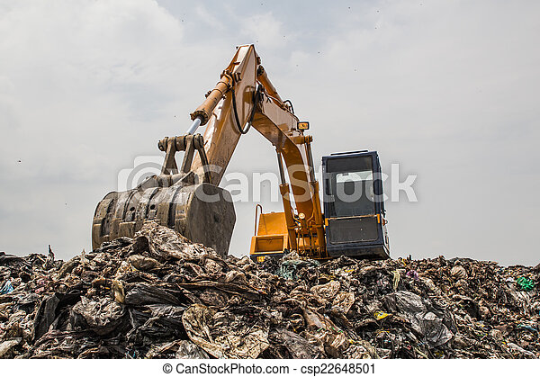 mountain of garbage with working backhoe