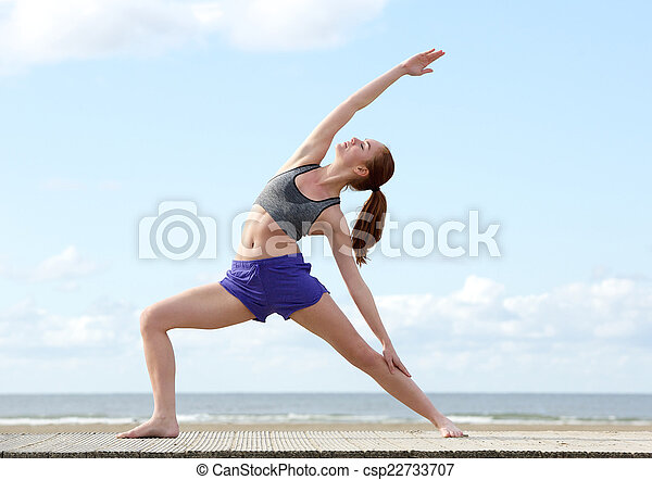 Woman stretching in yoga position at the beach