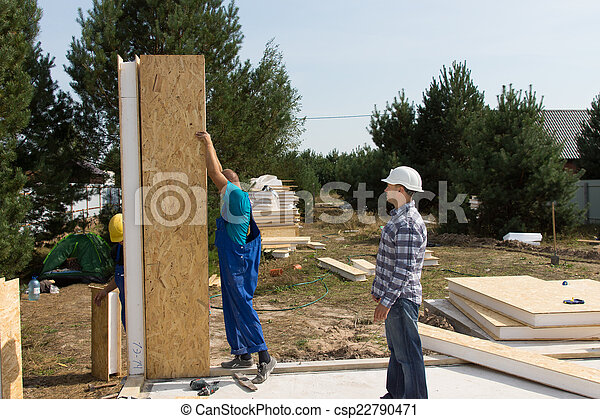 Builders erecting insulated wall panels