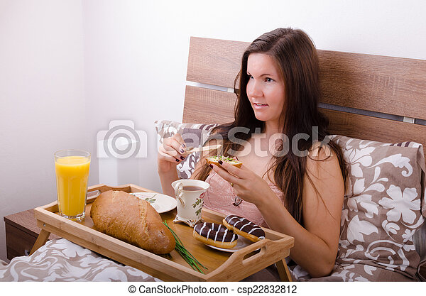 Beautiful young woman eating breakfast in bed in the morning