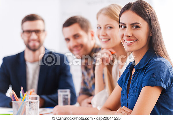 We are the team you can trust. Group of confident business people in smart casual wear sitting at the table together and smiling