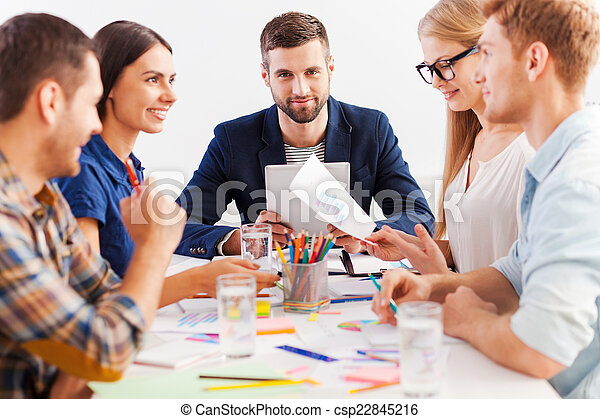 Working as team. Three confident business people in smart casual wear working together while sitting at the table