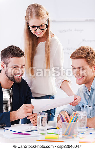 Discussing new project. Three confident business people in smart casual wear discussing something while looking at the document together