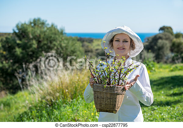 Woman  holding a pot with plant - csp22877795