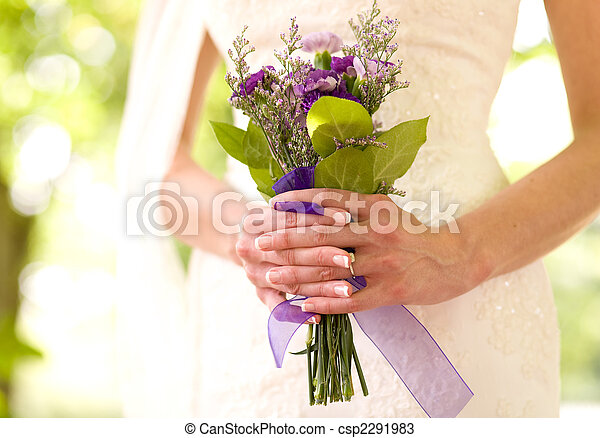 A bride holds a bouquet of flowers.  A very narrow depth of field, and high-key exposure are used. - csp2291983