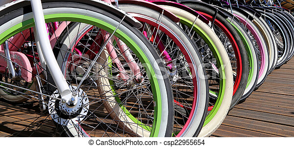 row multicolored bicycle wheels closeup