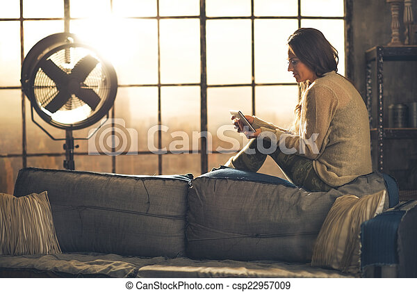 Young woman sitting in loft apartment and using tablet pc