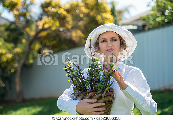 Woman holding a pot with plant - csp23006358