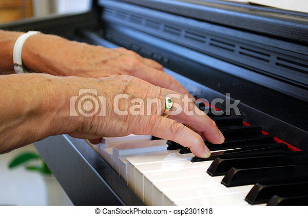two hands of an elderly woman playing piano - csp2301918