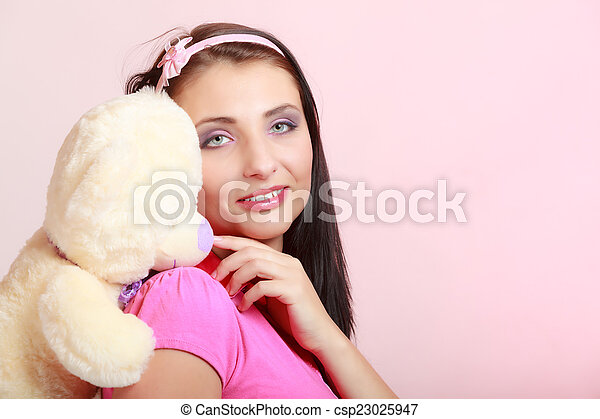 Childish young woman infantile girl in pink hugging teddy bear toy