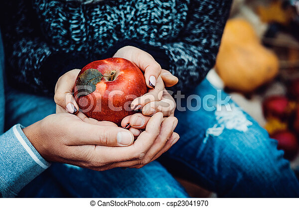 Beautiful young couple holding red apple
