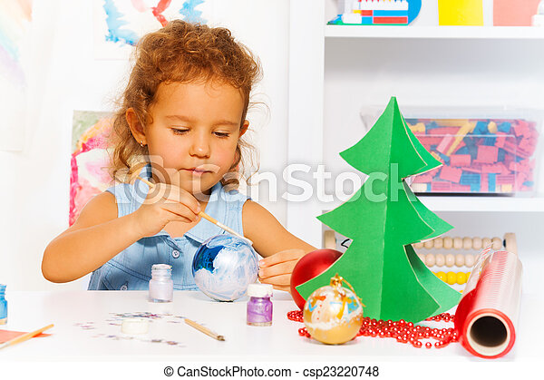 Cute small girl paints New Year ball for Xmas tree