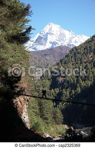 Porter crossing rope bridge in Himalaya, Nepal - csp2325369