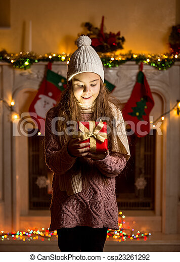 girl in wool sweater and hat looking inside of glowing present b
